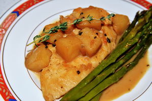 Plate containing chicken with apples and asparagus