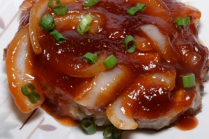 A plate containing a Chinese Style Pork Chop covered in a Sweet Onion Sauce