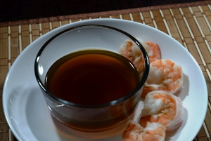 shrimp stock in a bowl on a plate with cooked shrimp