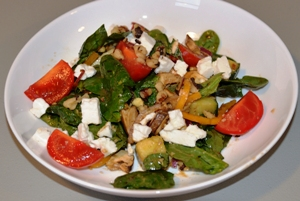 spinach salad in white bowl