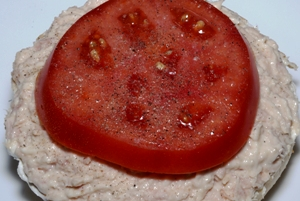 an open face bagel with cream cheese, tuna and tomato